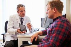 Paziente che ha consultazione con il dottore maschio In Office Fotografie Stock
