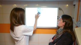 Paziente che osserva con medico l'immagine dei raggi x video d archivio