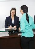 Paziente che registra all'ospedale di At Counter In del receptionist Fotografia Stock Libera da Diritti