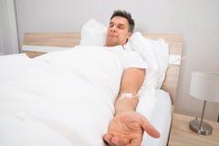Paziente che riposa sul letto con il gocciolamento del dispositivo di venipunzione immagine stock