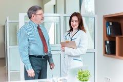 Paziente che sorride al suo medico in ufficio medico fotografia stock