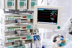Paziente con il monitor e le pompe per infusione in un ICU Fotografie Stock Libere da Diritti