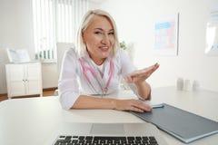 Paziente consultantesi di medico che utilizza video chiacchierata nella clinica immagine stock libera da diritti