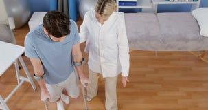 Paziente d'aiuto del fisioterapista da camminare con le grucce archivi video