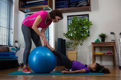 Paziente d'aiuto della ragazza del fisioterapista femminile nell'esercitarsi d'allungamento sulla stuoia di esercizio Immagine Stock Libera da Diritti