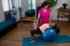 Paziente d'aiuto della ragazza del fisioterapista femminile nell'esercitarsi d'allungamento sulla stuoia di esercizio Fotografia Stock Libera da Diritti