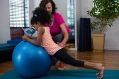 Paziente d'aiuto della ragazza del fisioterapista femminile nell'esercitarsi d'allungamento sulla stuoia di esercizio Fotografie Stock Libere da Diritti