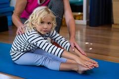 Paziente d'aiuto della ragazza del fisioterapista femminile nell'esercitarsi d'allungamento sulla stuoia di esercizio Fotografie Stock