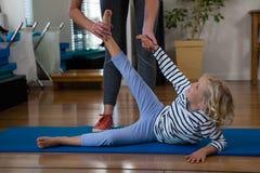 Paziente d'aiuto della ragazza del fisioterapista femminile nell'esercitarsi d'allungamento sulla stuoia di esercizio Immagini Stock