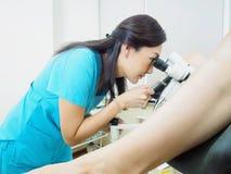 Paziente d'esame del ginecologo asiatico in ospedale facendo uso di un colposcope immagine stock