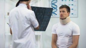 Paziente d'informazione del chirurgo femminile in collare cervicale della schiuma circa il cattivo risultato dei raggi x video d archivio
