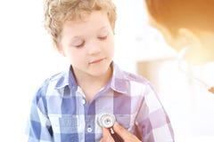 Paziente del bambino e di medico Il medico esamina il ragazzino secondo lo stetoscopio Concetto di terapia del ` s dei bambini e  Immagine Stock Libera da Diritti