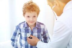 Paziente del bambino e di medico Il medico esamina il ragazzino secondo lo stetoscopio Concetto di terapia del ` s dei bambini e  Immagine Stock