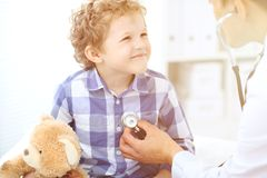 Paziente del bambino e di medico Il medico esamina il ragazzino secondo lo stetoscopio Concetto di terapia del ` s dei bambini e  Immagini Stock