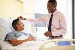 Paziente del dottore Talking To Male nella stanza di ospedale Fotografie Stock