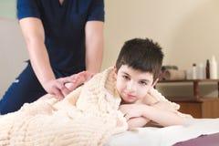 Paziente del ragazzino alla ricezione ad una massaggiatrice professionista Terapia di massaggio del piede immagini stock