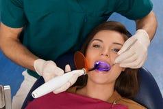 Paziente della donna alla chirurgia del dentista Immagine Stock
