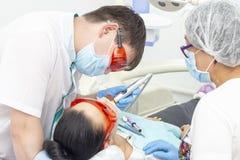Paziente della ragazza alla ricezione al trattamento del dentista del dente cariato la ragazza si trova sulla sedia dentaria con  fotografia stock
