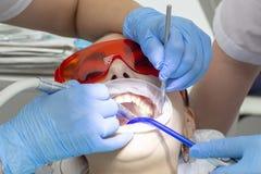 Paziente della ragazza alla ricezione al trattamento del dentista del dente cariato la ragazza si trova sulla sedia dentaria con  fotografie stock