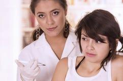 Paziente della ragazza che ottiene un colpo dall'infermiere Immagini Stock