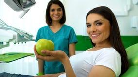 Paziente di signora che tiene mela verde e che sorride alla macchina fotografica, cura professionale dei denti immagine stock