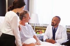 Paziente e moglie del dottore Talking To Male nel letto di ospedale fotografie stock libere da diritti