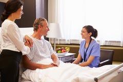 Paziente e moglie di Talking To Male dell'infermiere nel letto di ospedale immagini stock libere da diritti