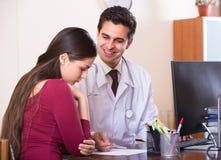 Paziente e therapeutist allo scrittorio in clinica Fotografia Stock