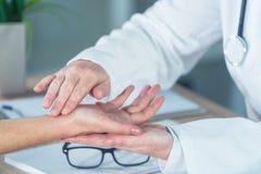 Paziente femminile all'esame medico di medico ortopedico per il injur del polso immagine stock