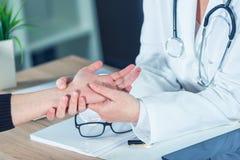 Paziente femminile all'esame medico di medico ortopedico per il injur del polso fotografia stock