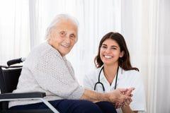 Paziente femminile del dottore With Disabled Senior in ospedale fotografie stock libere da diritti