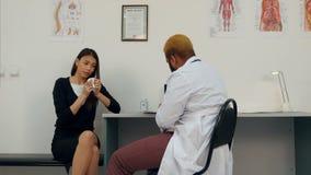 Paziente femminile malato di starnuto che ascolta il medico che fa le note stock footage