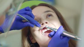 Paziente femminile sulla procedura di pulizia dei denti Lavoro delle mani del dentista video d archivio
