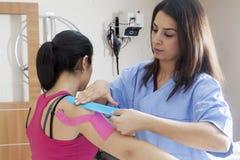 Paziente a fisioterapia con nastri adesivi Fotografie Stock Libere da Diritti