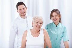 Paziente geriatrico con i suoi fisioterapisti Fotografia Stock
