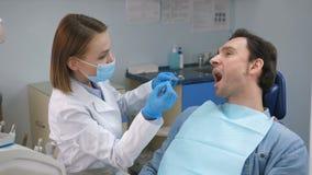 Paziente incoraggiante del dentista prima del controllo generale in ufficio archivi video