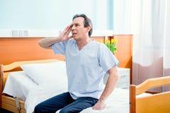 Paziente invecchiato con l'emicrania che si siede sul letto nella camera in ospedale Immagini Stock