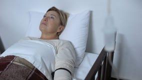 Paziente invecchiato triste che si trova nel letto di ammalato sotto il contagoccia, analgesia controllata dal paziente stock footage