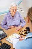 Paziente maggiore della donna con l'infermiera BRITANNICA Immagine Stock Libera da Diritti