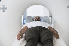 Paziente maschio che subisce ricerca di CT nella stanza dell'esame immagini stock