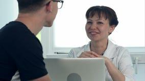 Paziente maschio consultantesi di medico femminile amichevole che si siede allo scrittorio con il computer portatile video d archivio