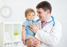 Paziente maschio del neonato della tenuta del pediatra fotografia stock