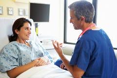 Paziente maschio di Talking With Female dell'infermiere nella stanza di ospedale Fotografie Stock Libere da Diritti