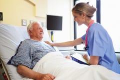 Paziente maschio di Talking To Senior dell'infermiere nella stanza di ospedale Fotografie Stock