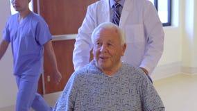 Paziente maschio senior che è inserito la sedia a rotelle da medico video d archivio