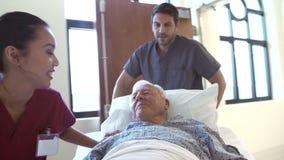 Paziente maschio senior che è spinto lungo il corridoio dell'ospedale video d archivio