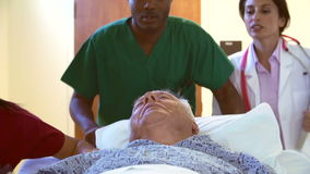 Paziente maschio senior che è spinto lungo il corridoio dell'ospedale stock footage