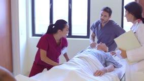 Paziente maschio senior che è spinto lungo il corridoio dell'ospedale archivi video