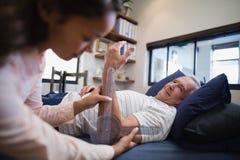 Paziente maschio senior che esamina il gomito di misurazione di medico femminile fotografia stock libera da diritti