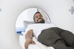 Paziente maschio sorridente che subisce ricerca di CT nella stanza dell'esame immagine stock libera da diritti
